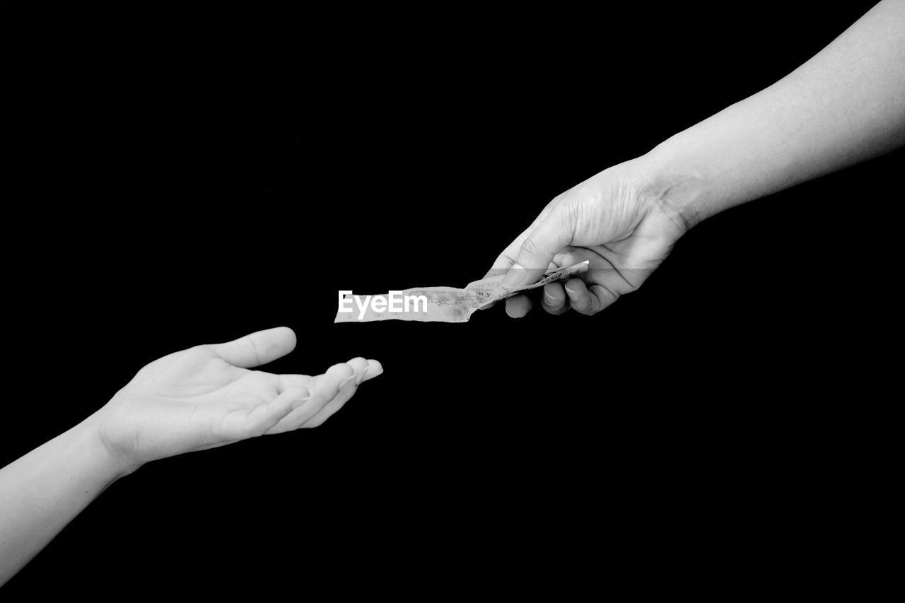 Close-up of hand giving money to friend over black background