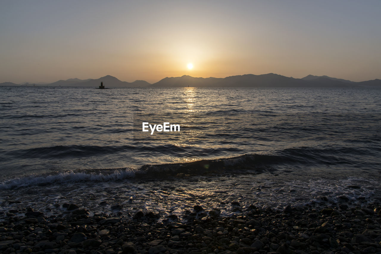 sunset, sky, water, beauty in nature, tranquility, scenics - nature, sea, tranquil scene, mountain, beach, land, nature, no people, sunlight, sun, idyllic, outdoors, clear sky, non-urban scene