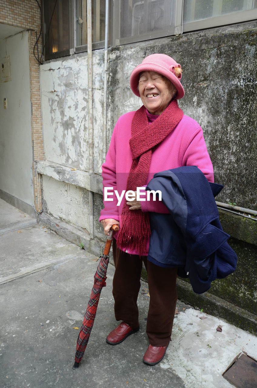 Cheerful senior woman wearing hat against wall