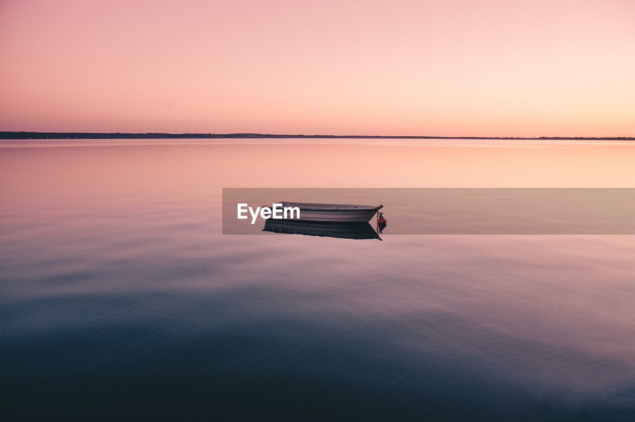 tranquility, beauty in nature, tranquil scene, nature, sunset, reflection, scenics, water, idyllic, sky, copy space, no people, sea, outdoors, waterfront, clear sky, horizon over water, symmetry, day