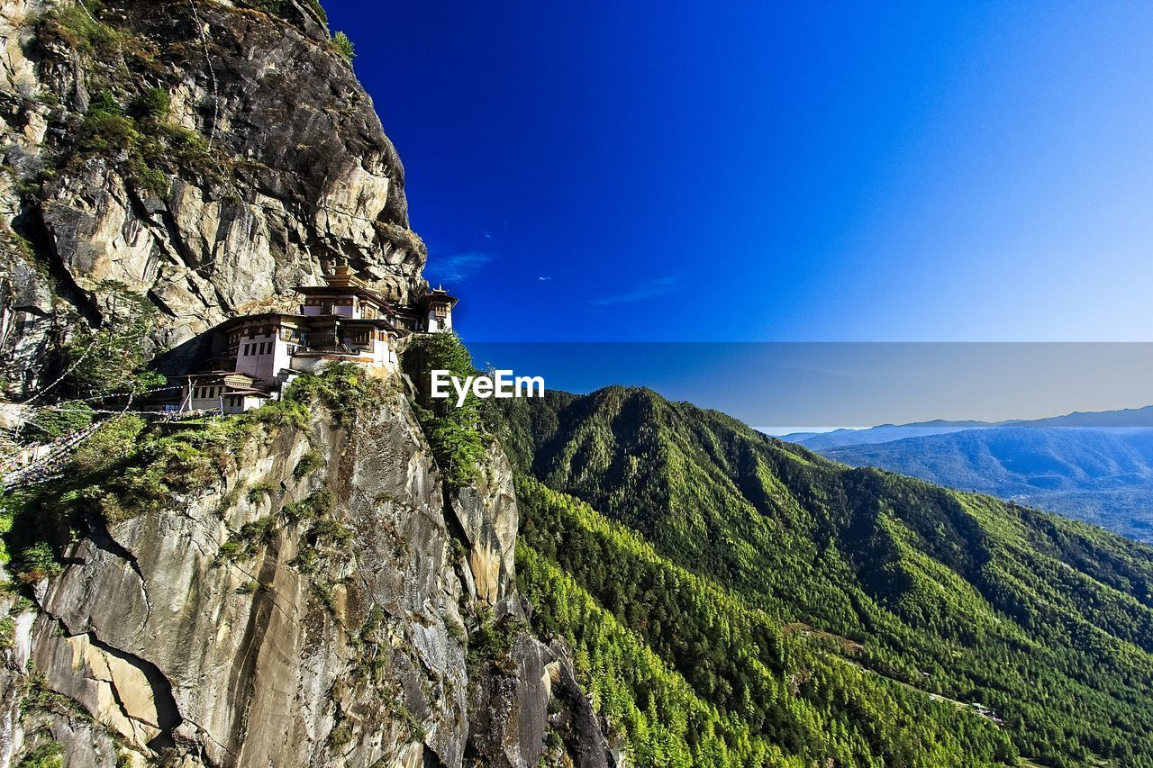 Scenic view of tigers nest monastery with mountains against blue sky