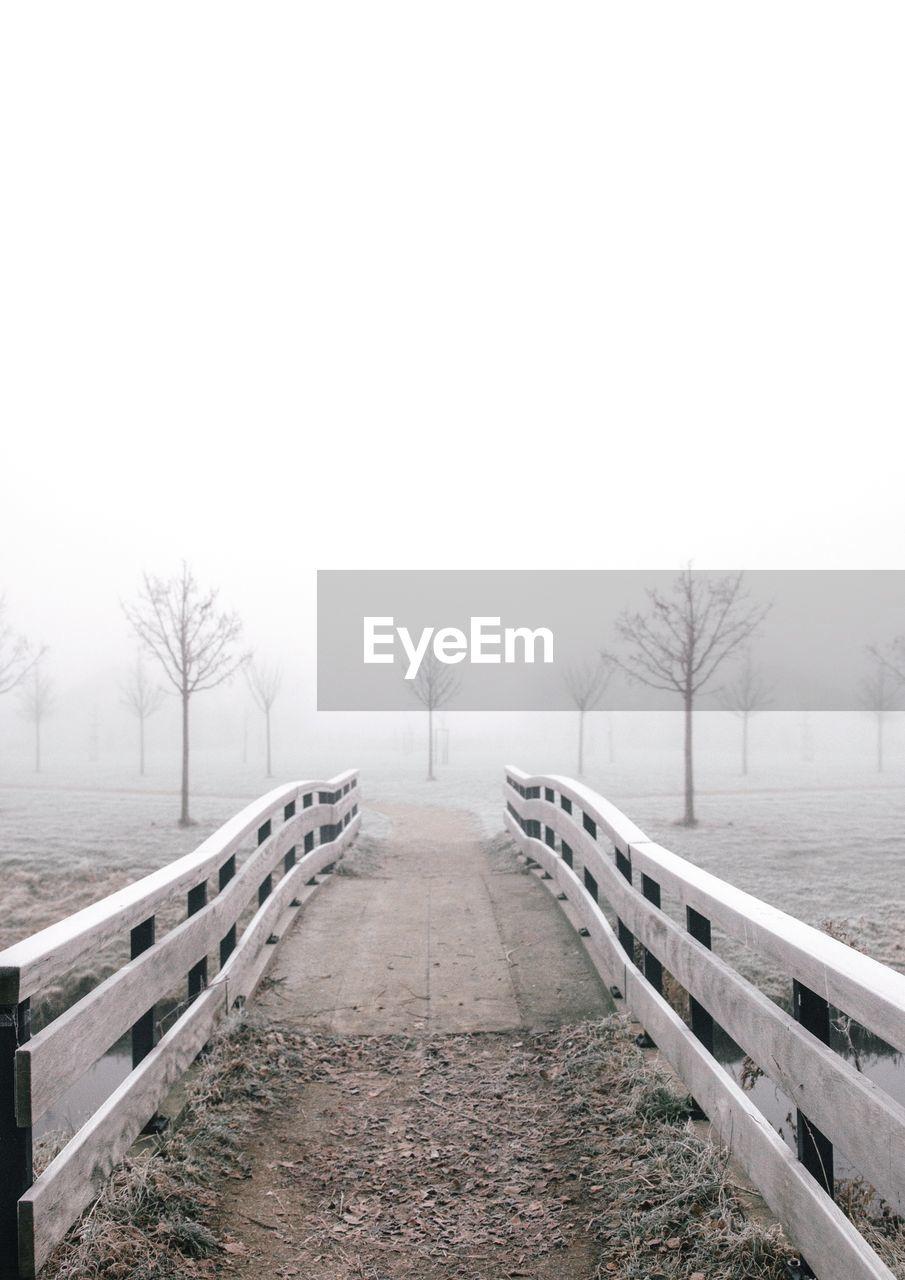 Footbridge on foggy landscape against sky