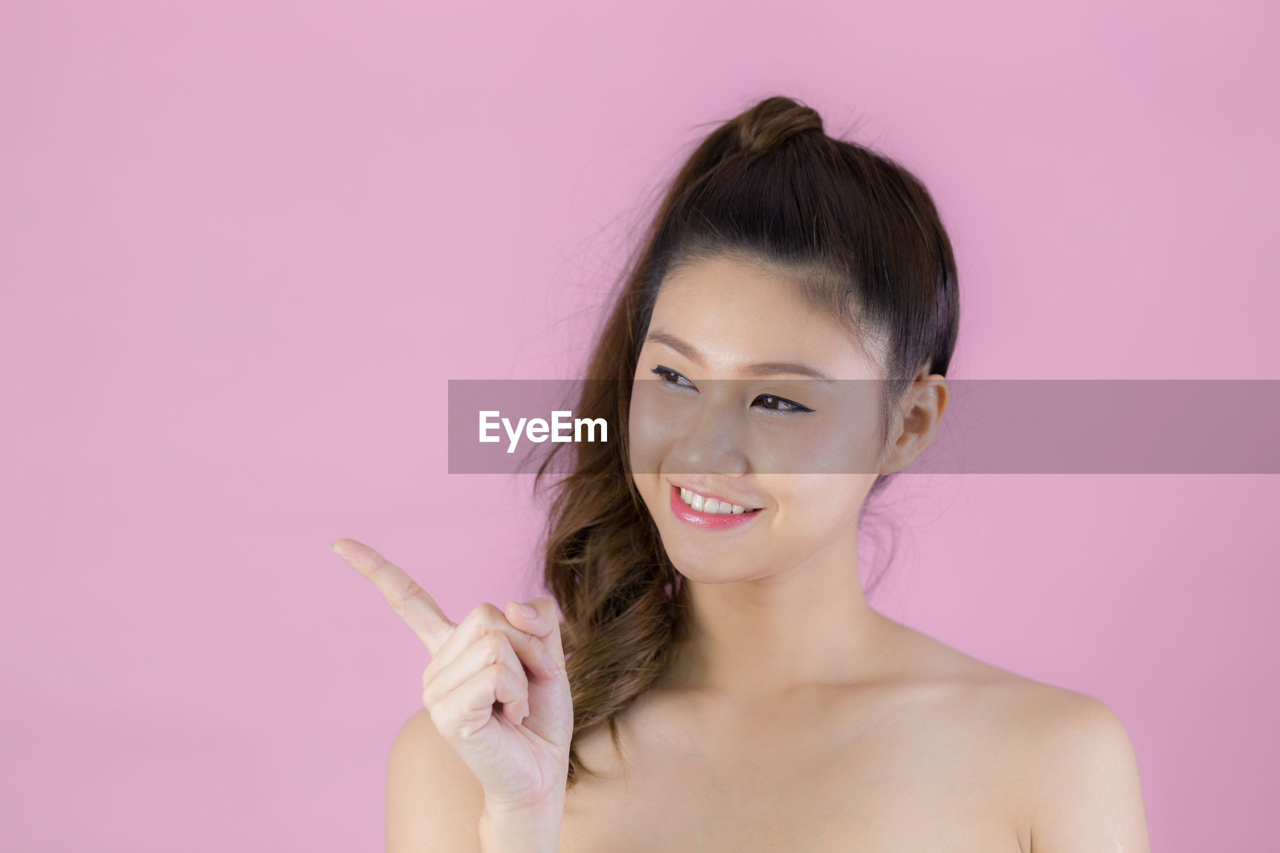 Smiling shirtless woman pointing against pink background