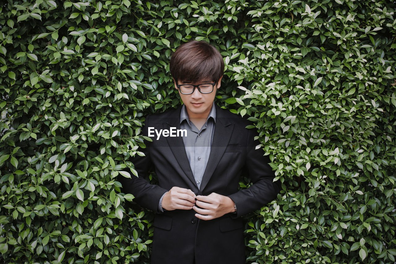 A young asian groom looked down at his hand wearing a suit in front of the tree bush.