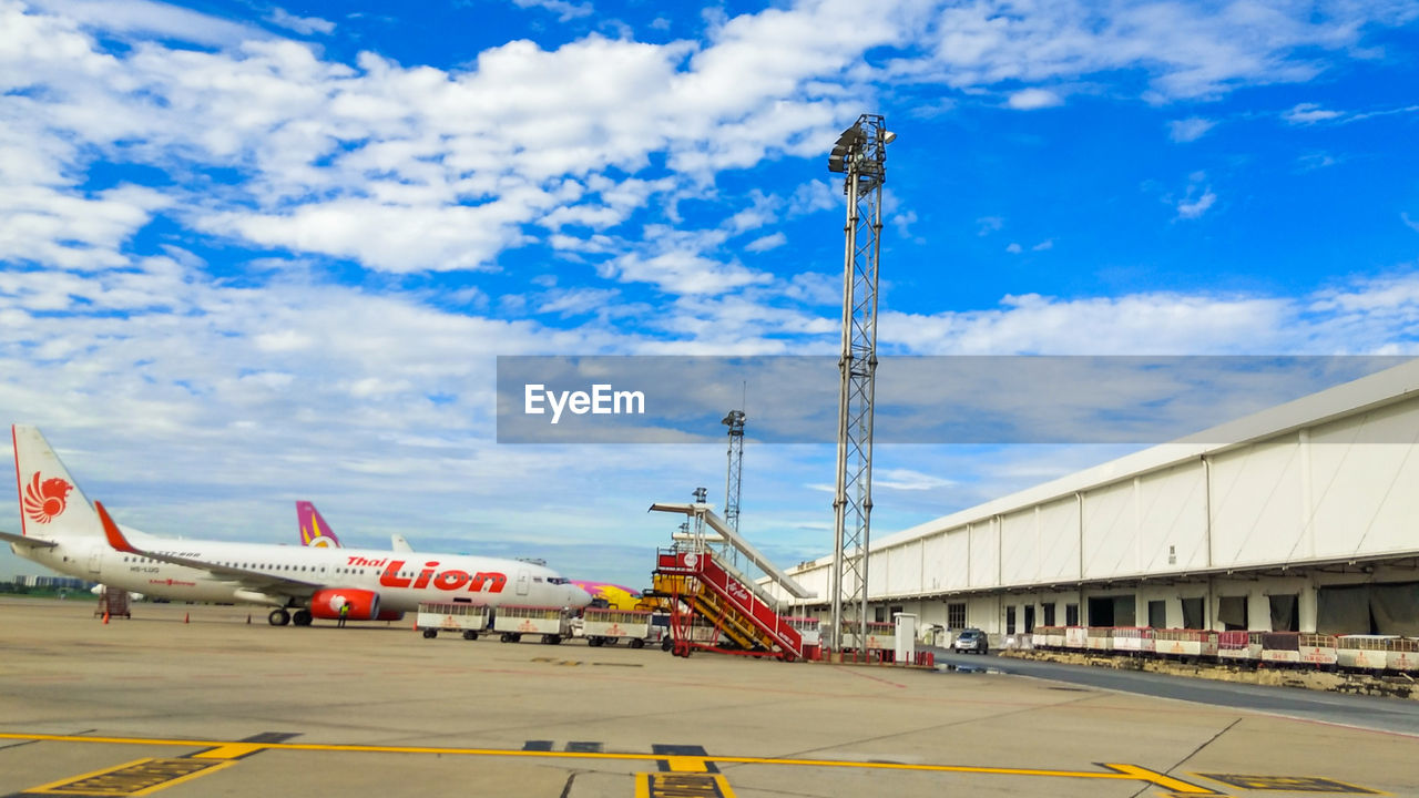 AIRPLANE AT AIRPORT AGAINST SKY