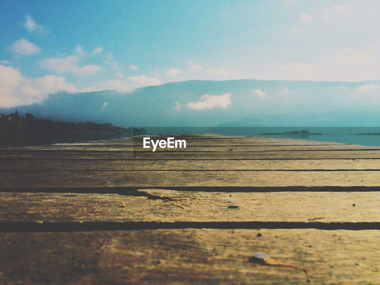 Wooden Pier By Mountains Against Sky