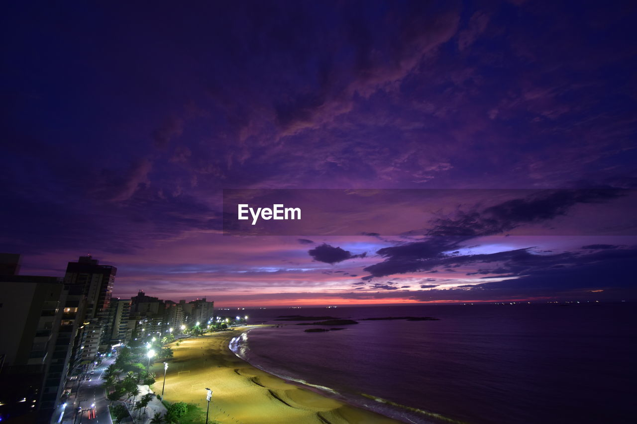 sky, cloud - sky, water, illuminated, building exterior, architecture, night, city, sunset, built structure, scenics - nature, nature, sea, beauty in nature, no people, outdoors, dramatic sky, dusk, beach, purple, cityscape