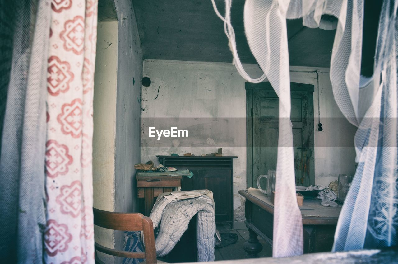 indoors, no people, curtain, textile, seat, furniture, chair, window, architecture, abandoned, day, old, building, house, absence, domestic room, damaged, home interior, obsolete, run-down, messy, ruined