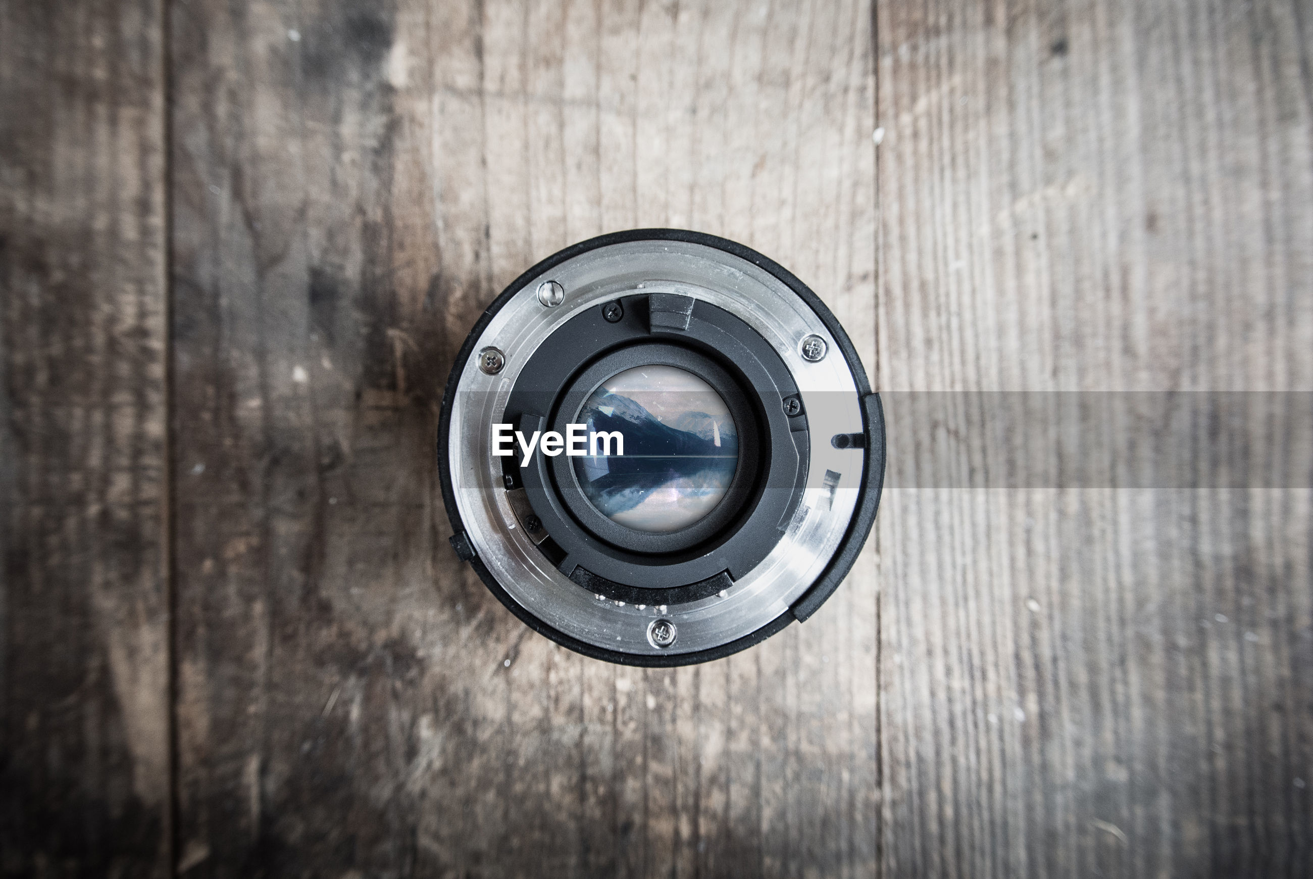 Directly above shot of camera lens on wooden table