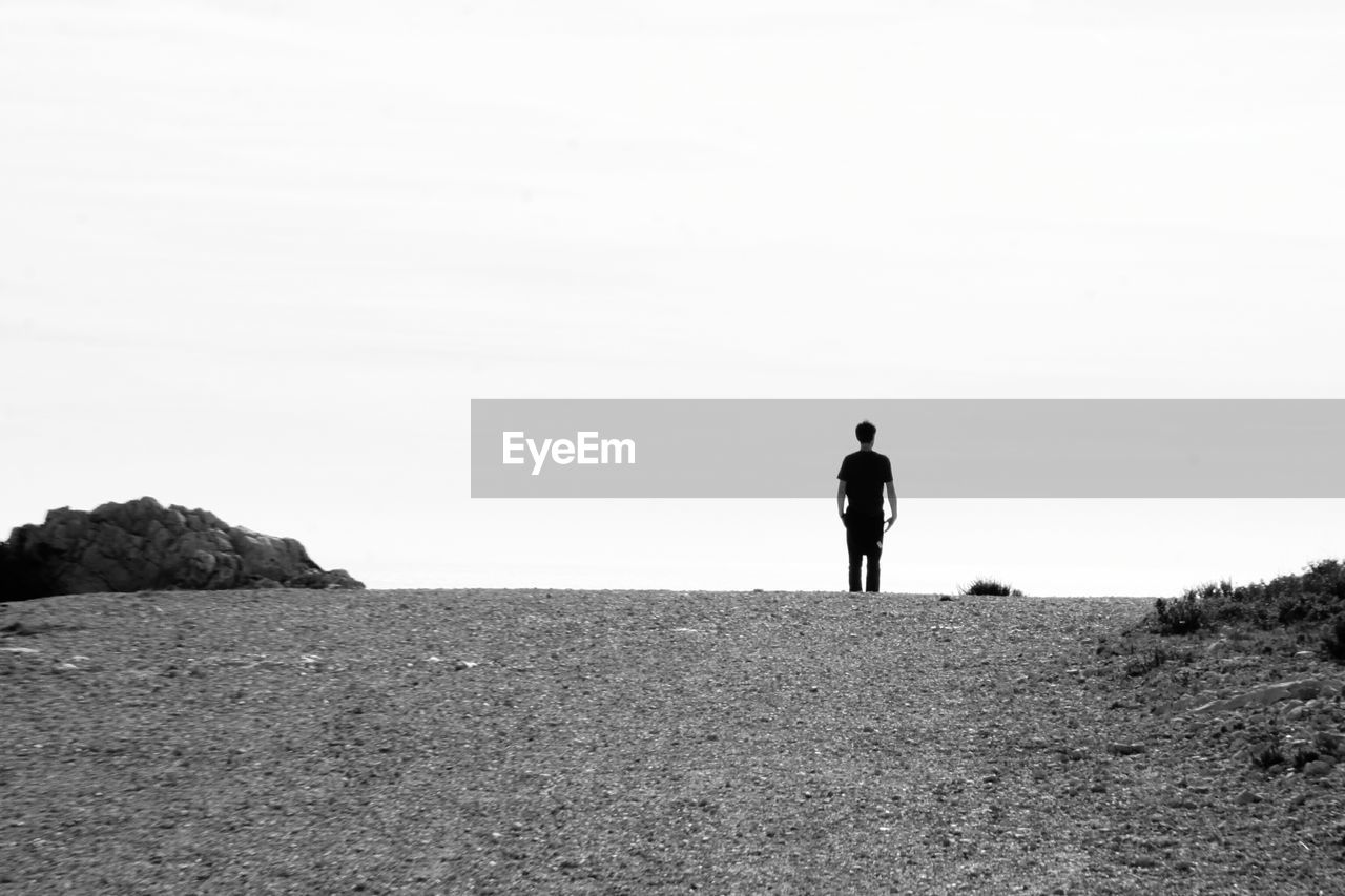 full length, one person, nature, rear view, walking, tranquil scene, standing, tranquility, scenics, real people, outdoors, men, day, beauty in nature, clear sky, landscape, sea, sky, one man only, people