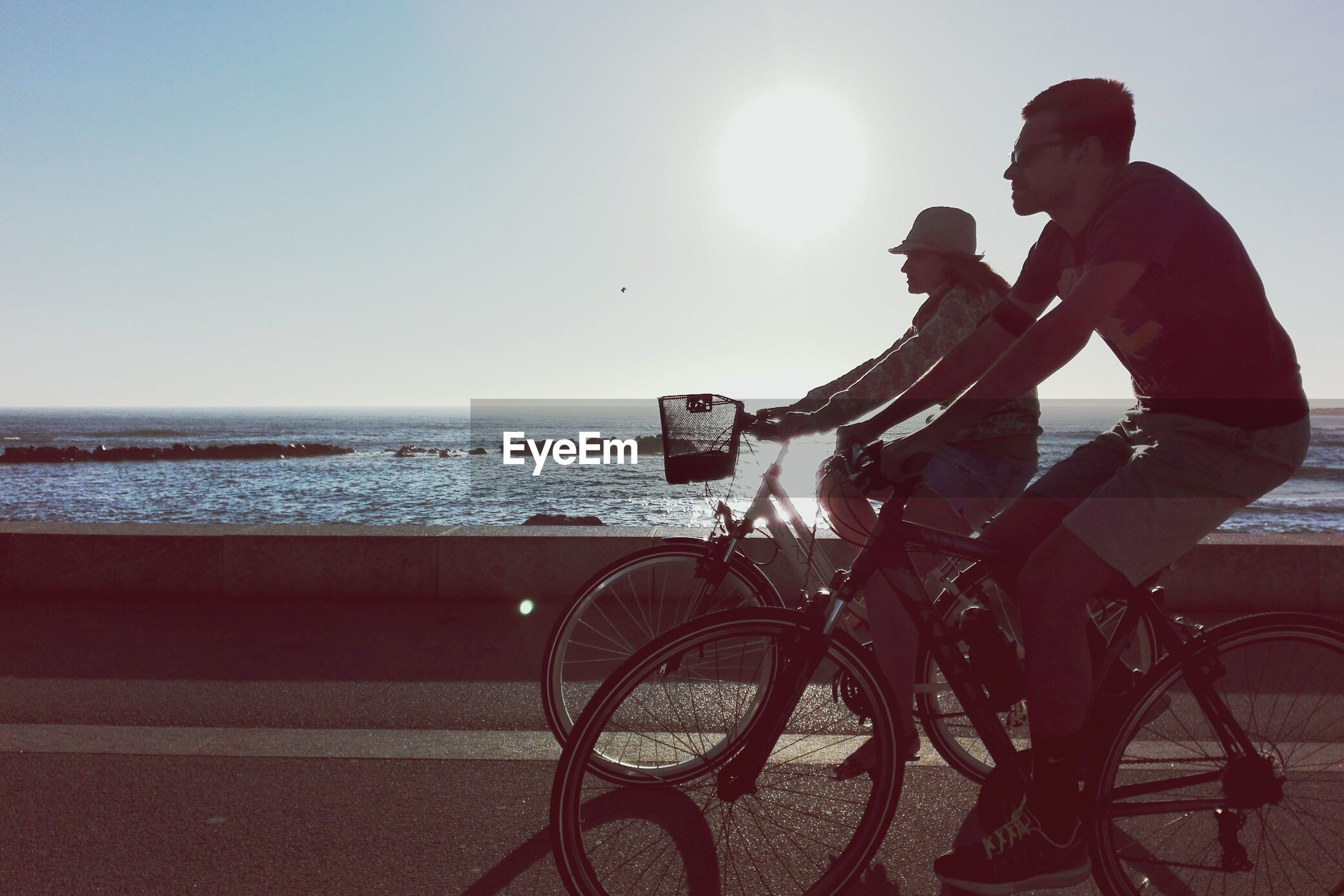 Man and woman cycling on road by sea against clear sky