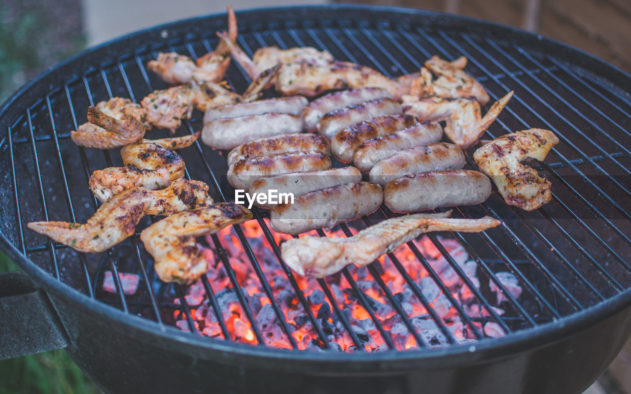 Close-Up Of Chicken Wings And Sausages On Barbecue Grill