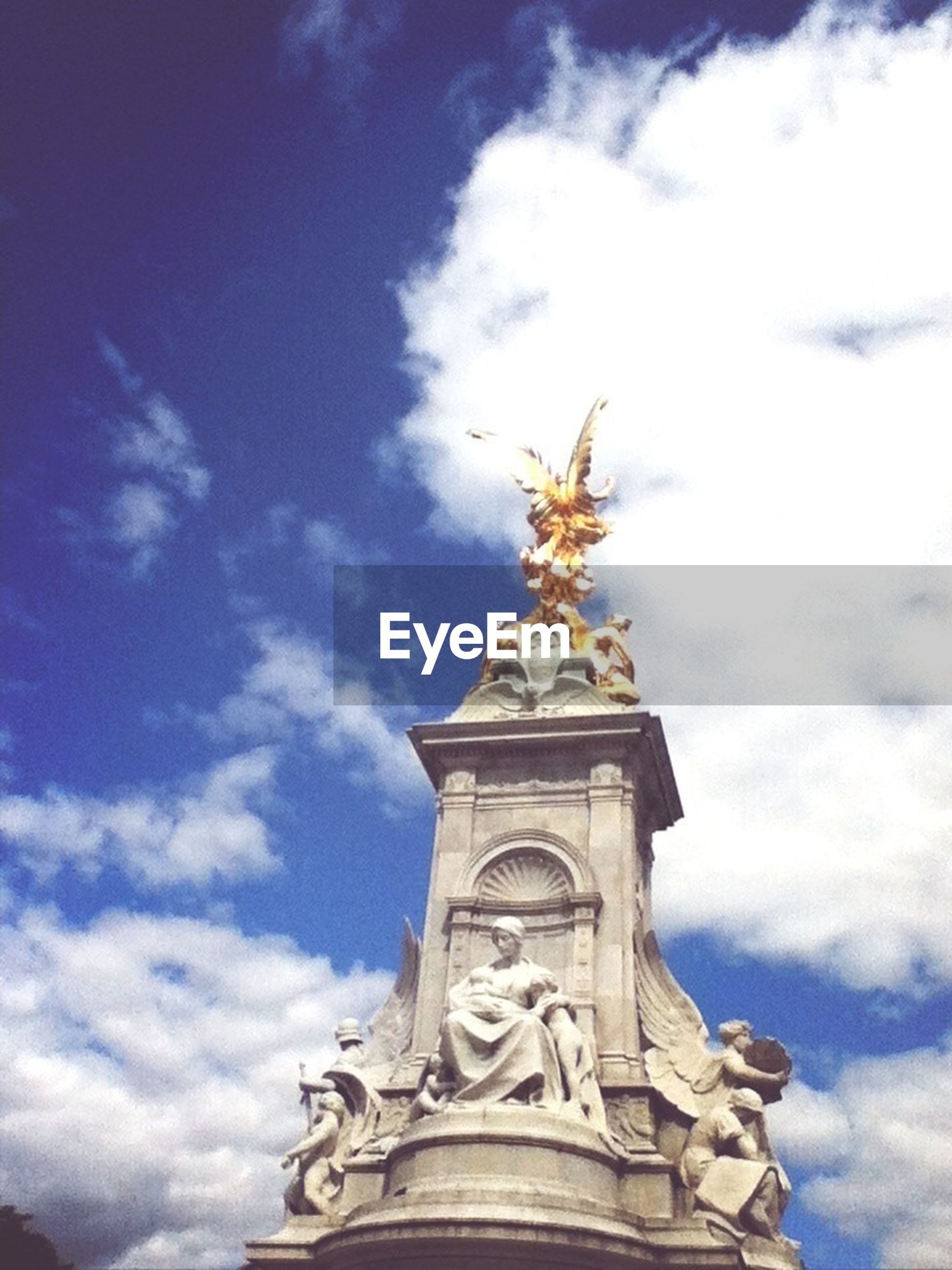 low angle view, statue, human representation, sculpture, art and craft, sky, art, cloud - sky, creativity, architecture, built structure, religion, place of worship, building exterior, cloud, spirituality, cloudy, history