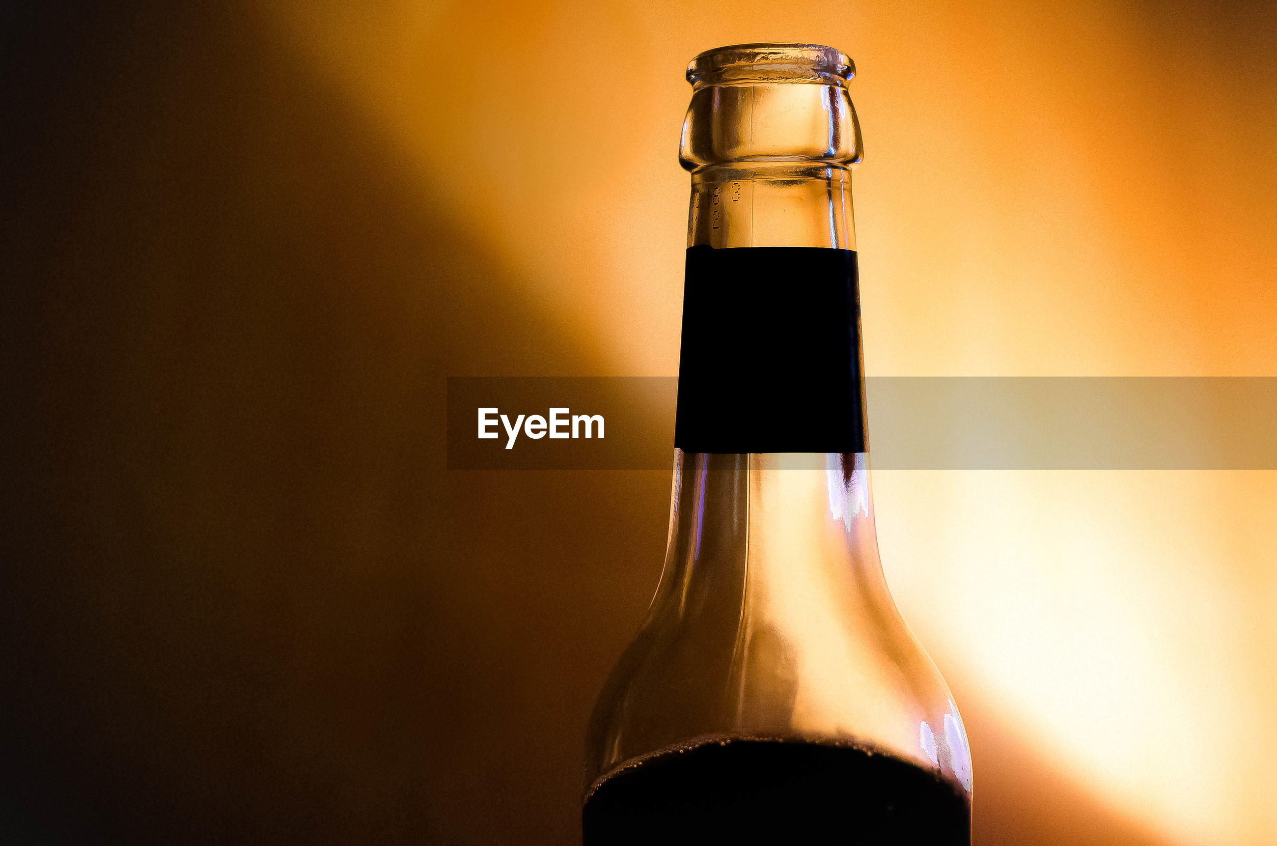 CLOSE-UP OF BEER GLASS BOTTLE AGAINST GRAY BACKGROUND