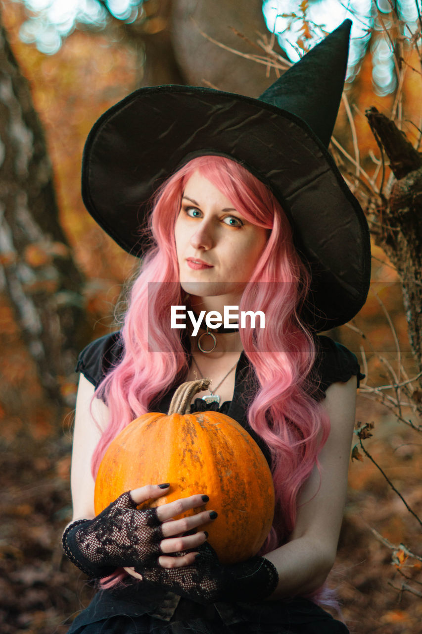 Portrait of beautiful young woman holding pumpkin