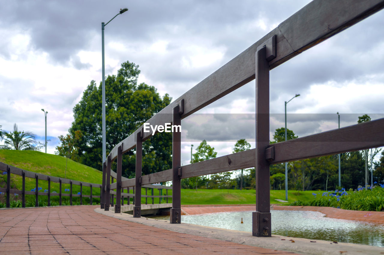 Walkway against cloudy sky at park