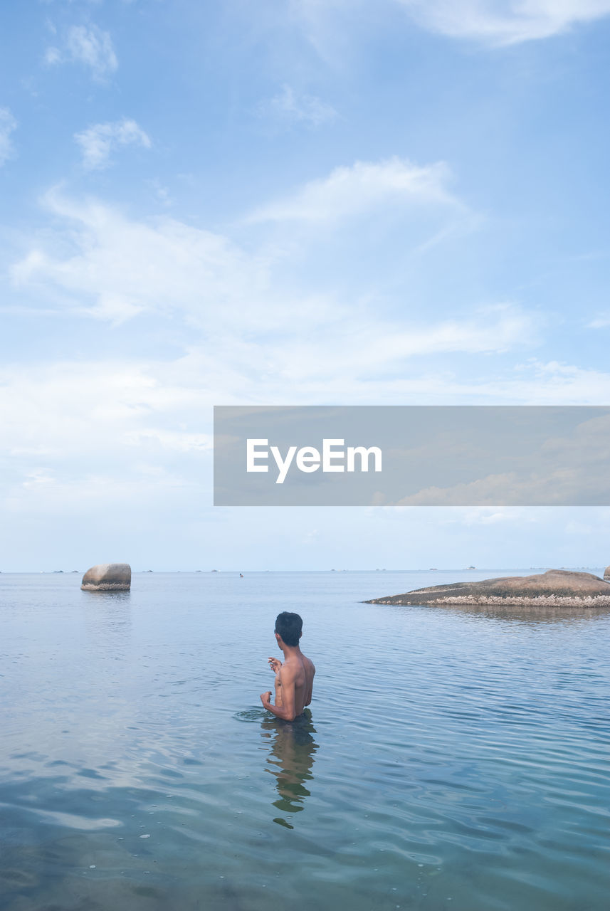 Shirtless Man Standing In Water At Beach Against Sky