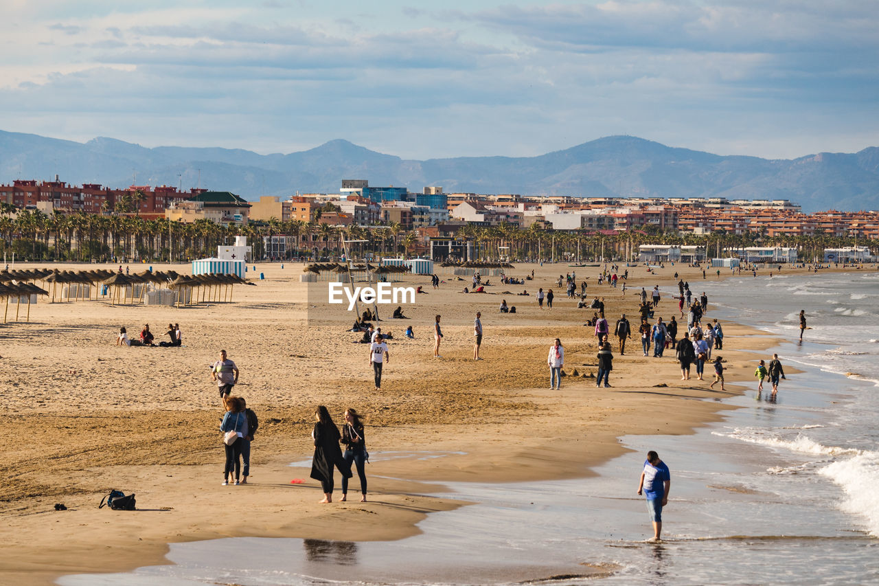 group of people, real people, large group of people, crowd, water, nature, land, beach, day, sky, men, architecture, leisure activity, built structure, women, lifestyles, cloud - sky, mountain, outdoors