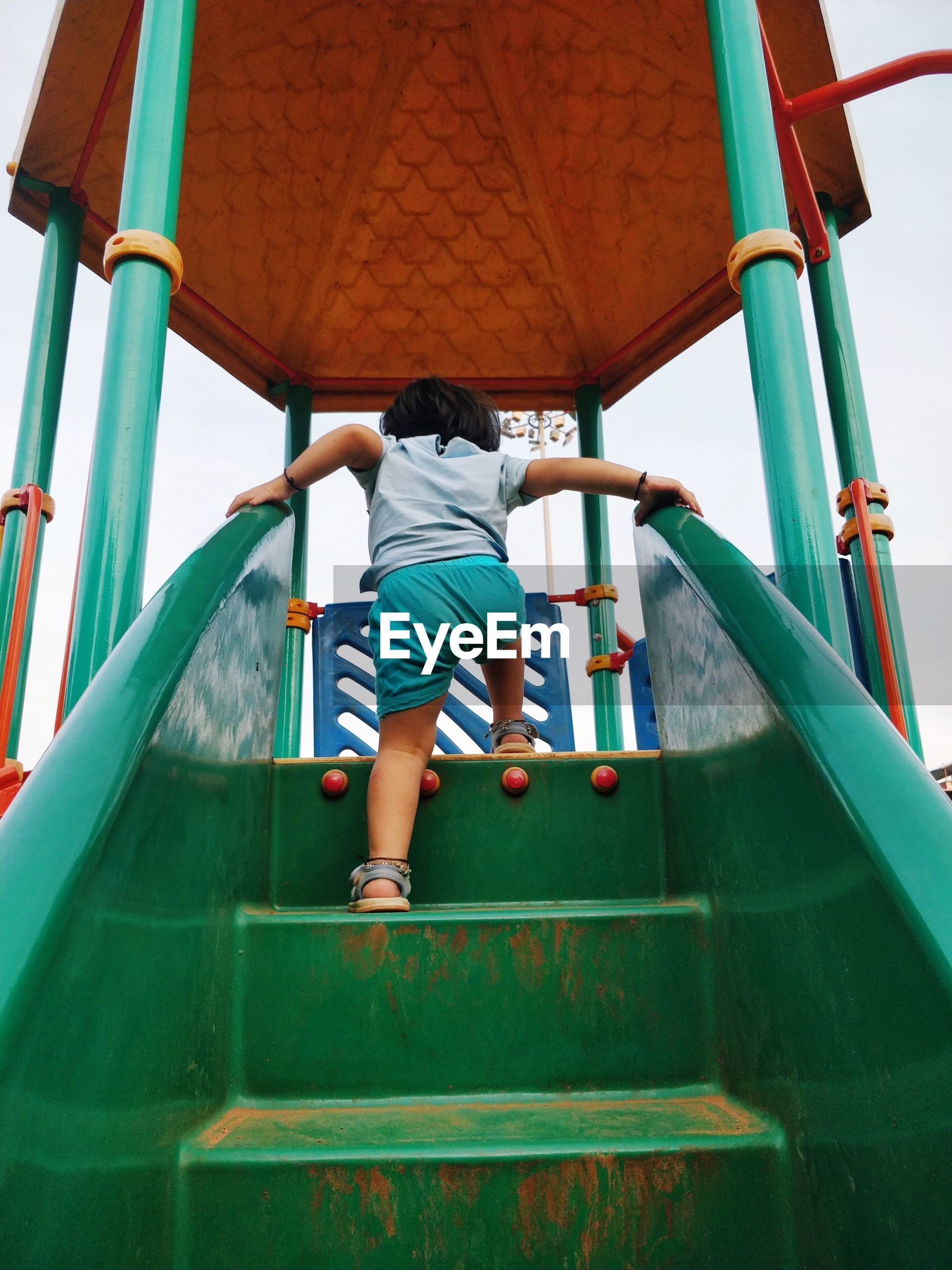 Rear view of boy playing on outdoor play equipment