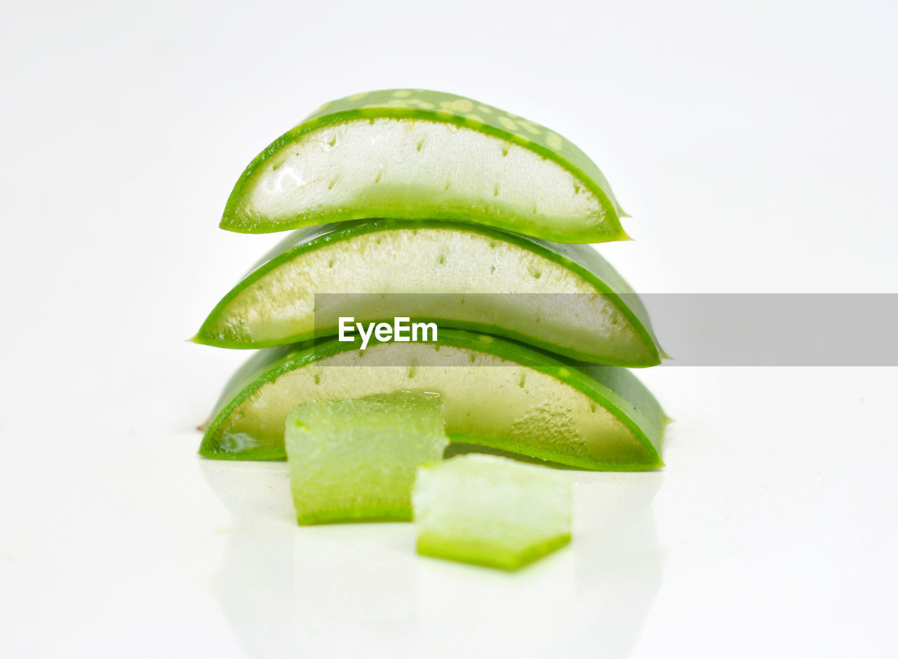 white background, slice, food and drink, studio shot, healthy eating, food, freshness, wellbeing, green color, no people, close-up, vegetable, still life, indoors, cucumber, fruit, group of objects, copy space, cross section, cut out