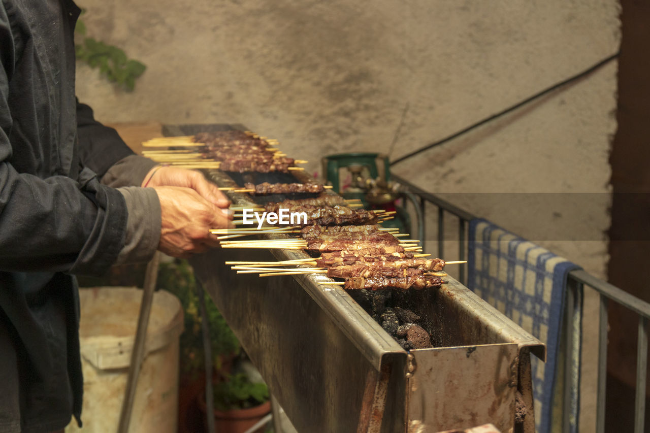 Midsection of man cooking food on barbecue grill