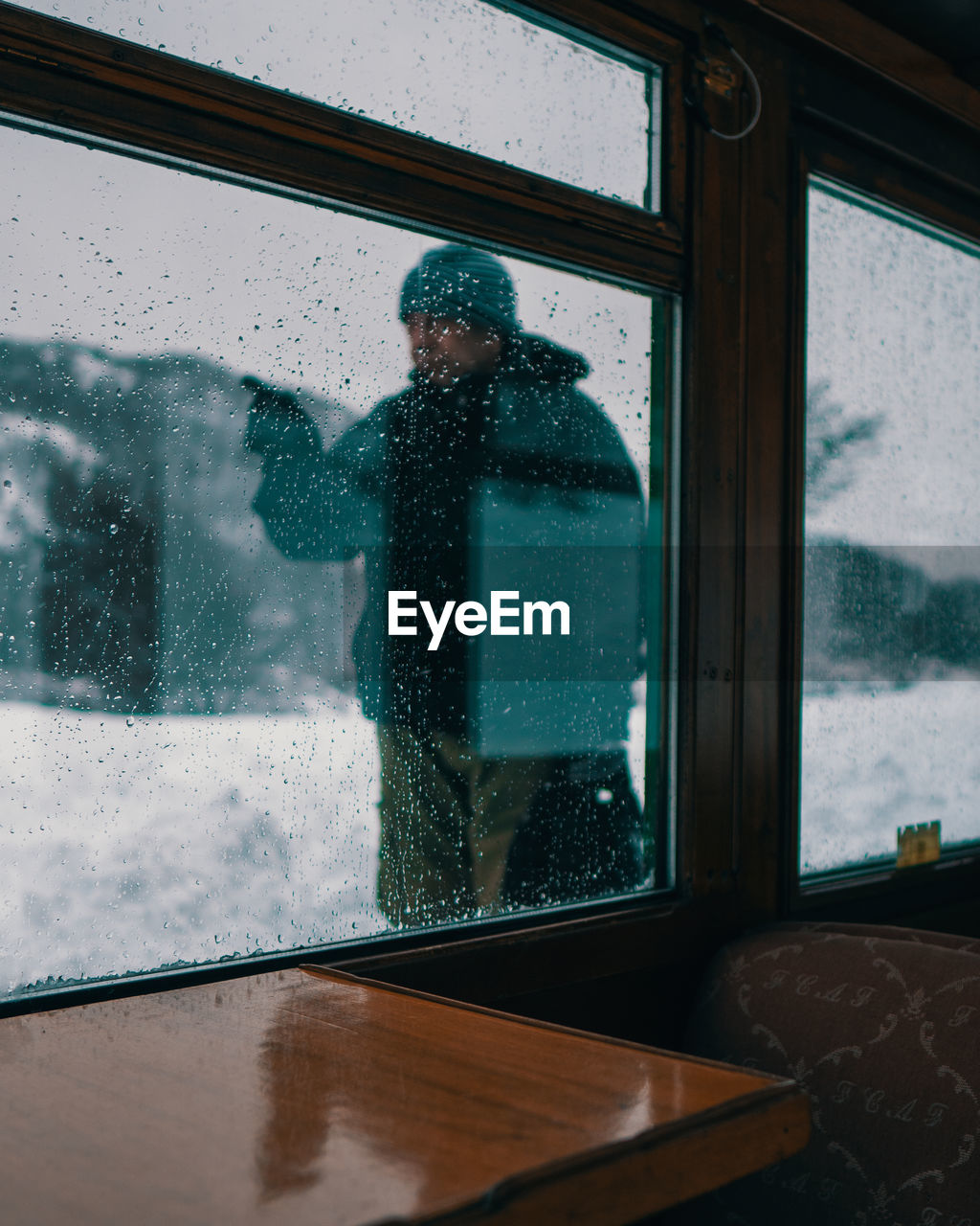 REFLECTION OF MAN LOOKING THROUGH WINDOW