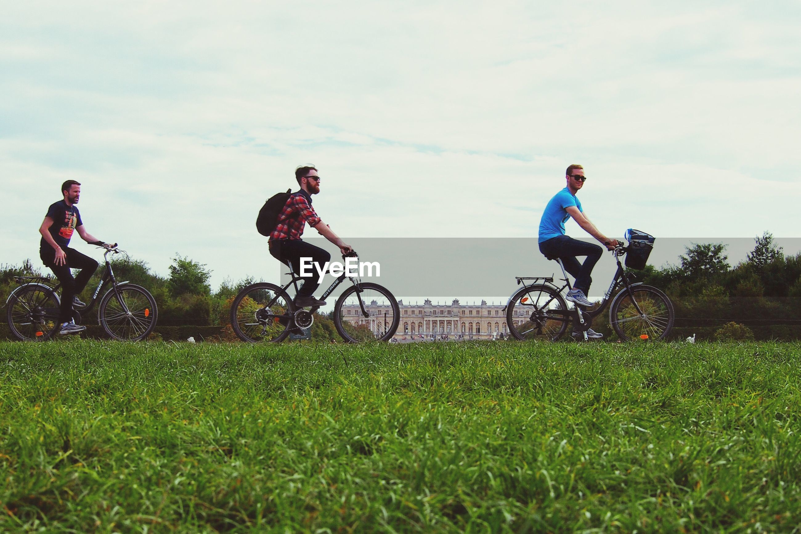 lifestyles, bicycle, leisure activity, transportation, land vehicle, mode of transport, riding, men, full length, grass, casual clothing, sky, togetherness, motorcycle, cycling, field, travel