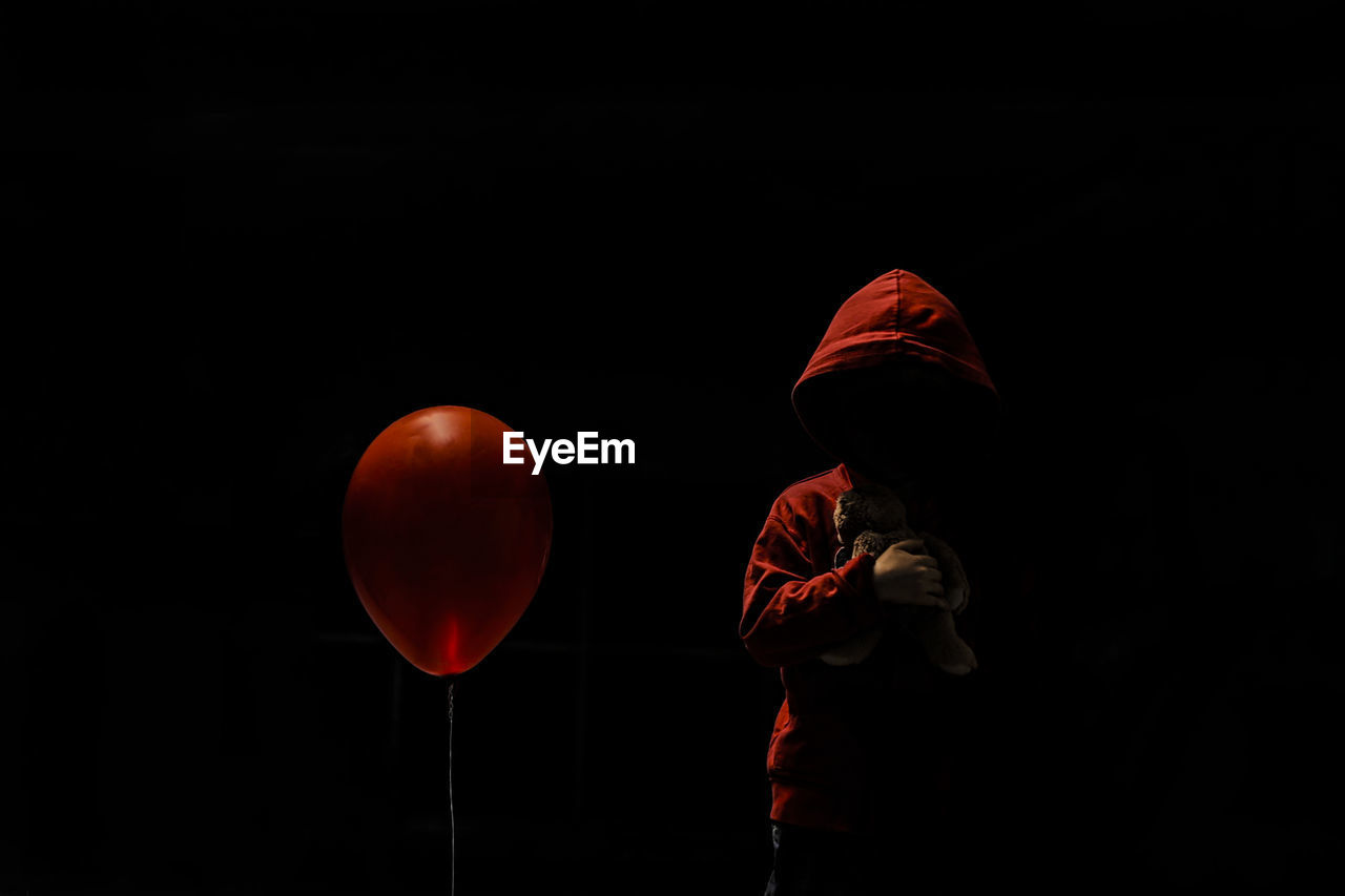 Boy Wearing Hood Holding Stuffed Toy While Standing By Red Balloon Against Black Background