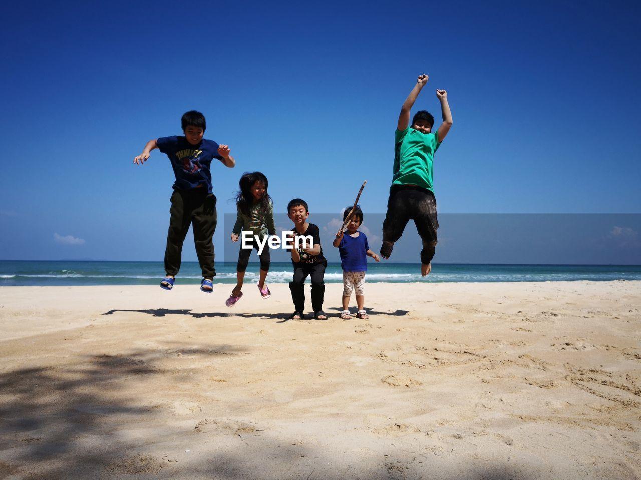 Siblings At Beach Against Clear Sky