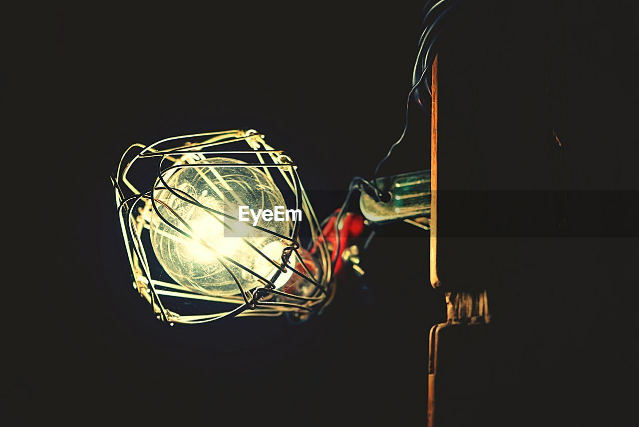 illuminated, lighting equipment, indoors, dark, glowing, electricity, light, black background, close-up, darkroom, copy space, studio shot, one person, electric light, night, light - natural phenomenon, domestic room, light bulb, technology