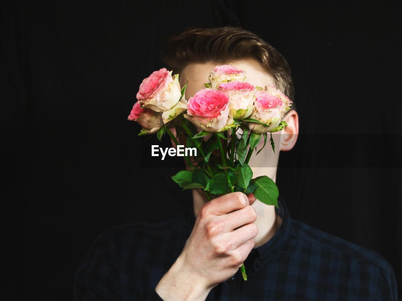 Man Holding Bouquet Against Black Background