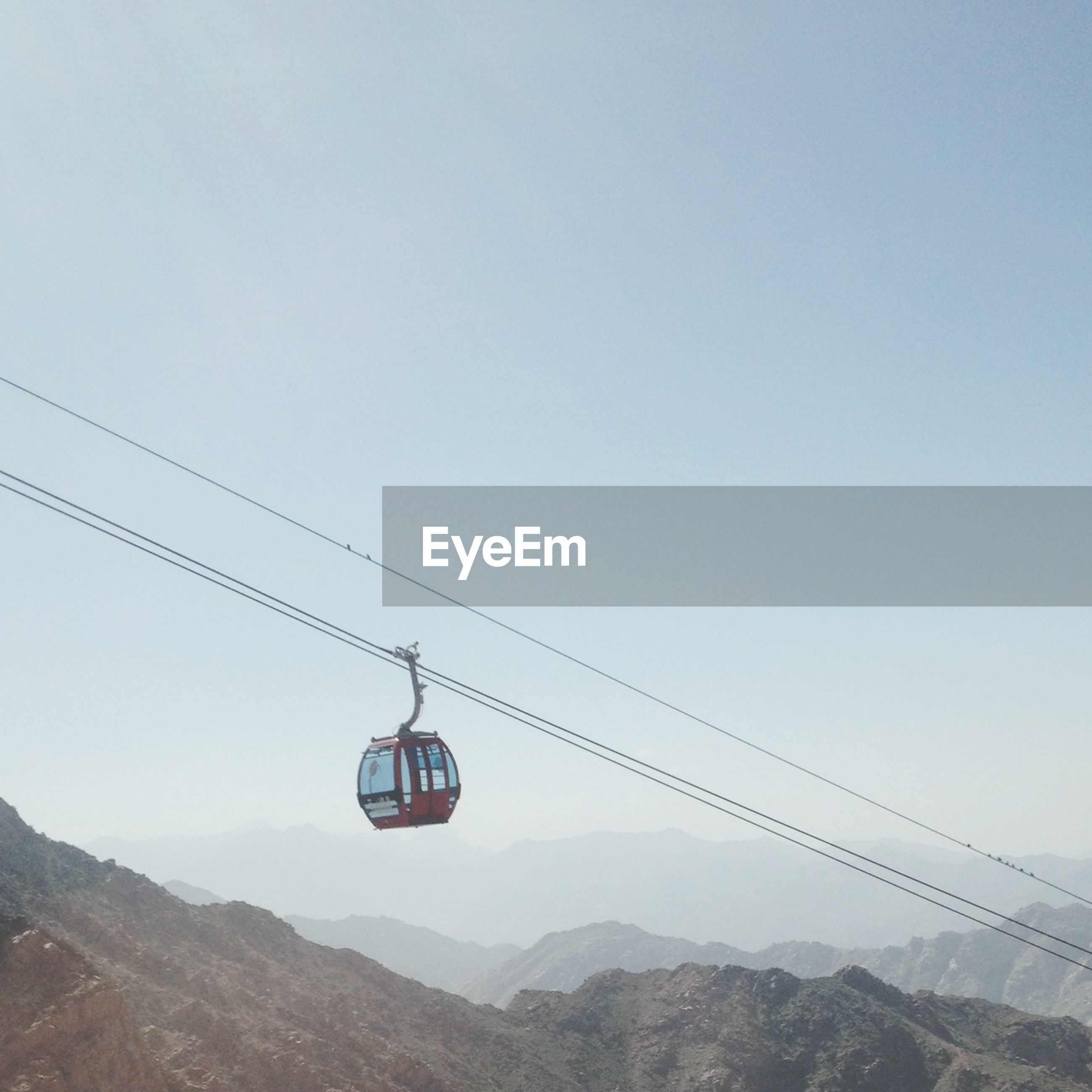 transportation, mountain, mode of transport, clear sky, copy space, adventure, overhead cable car, landscape, mountain range, extreme sports, mid-air, travel, scenics, flying, tranquility, low angle view, sky, nature, air vehicle