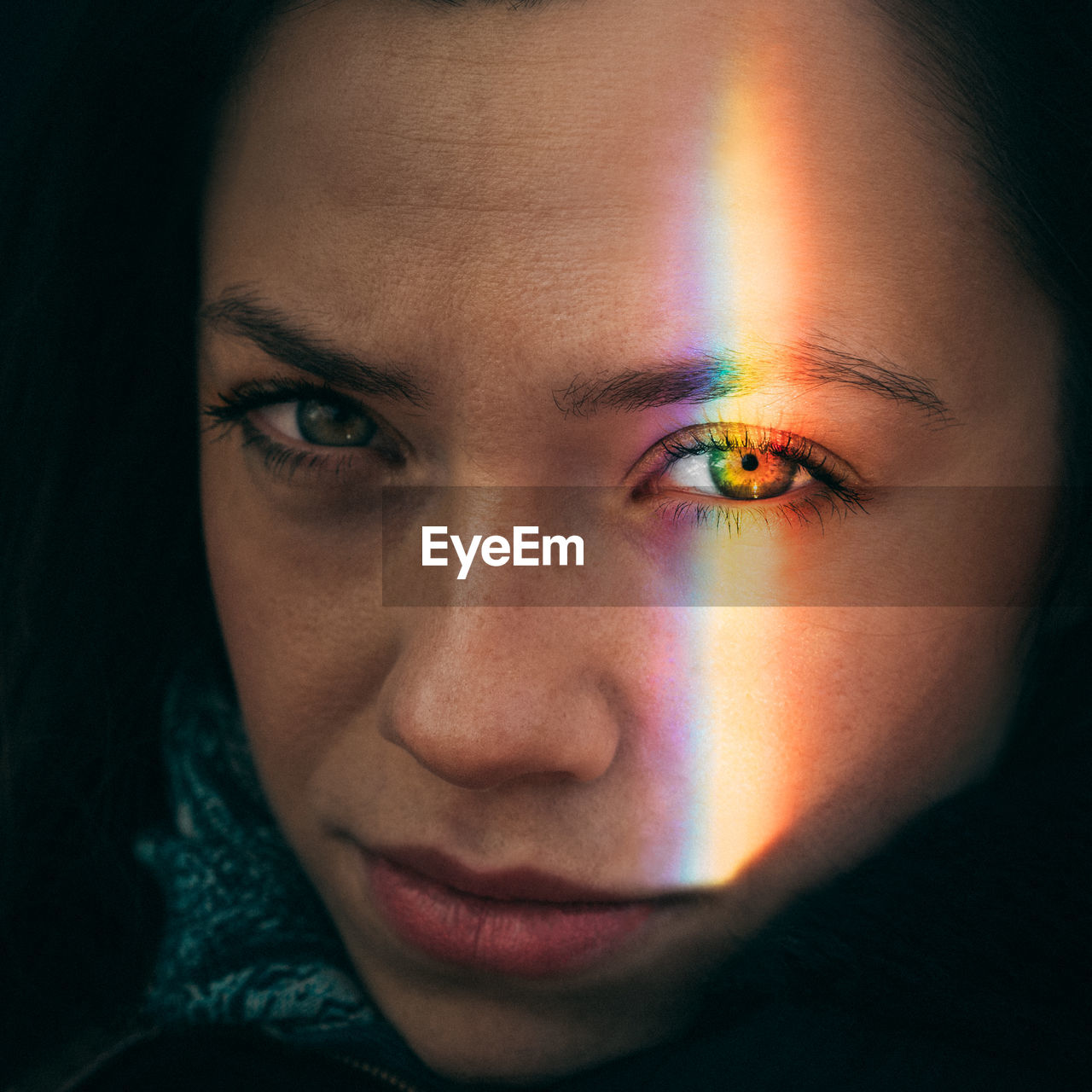 Close-Up Portrait Of Woman With Spectrum Falling On Face