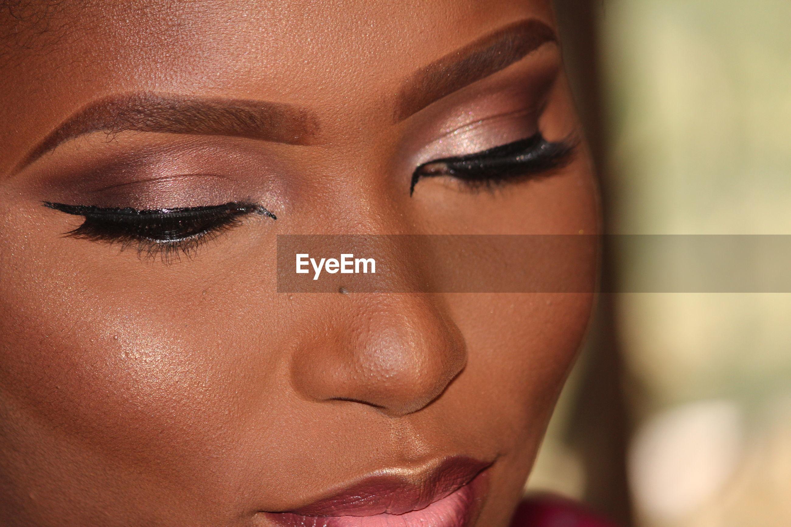 Close-up of woman wearing make-up at home