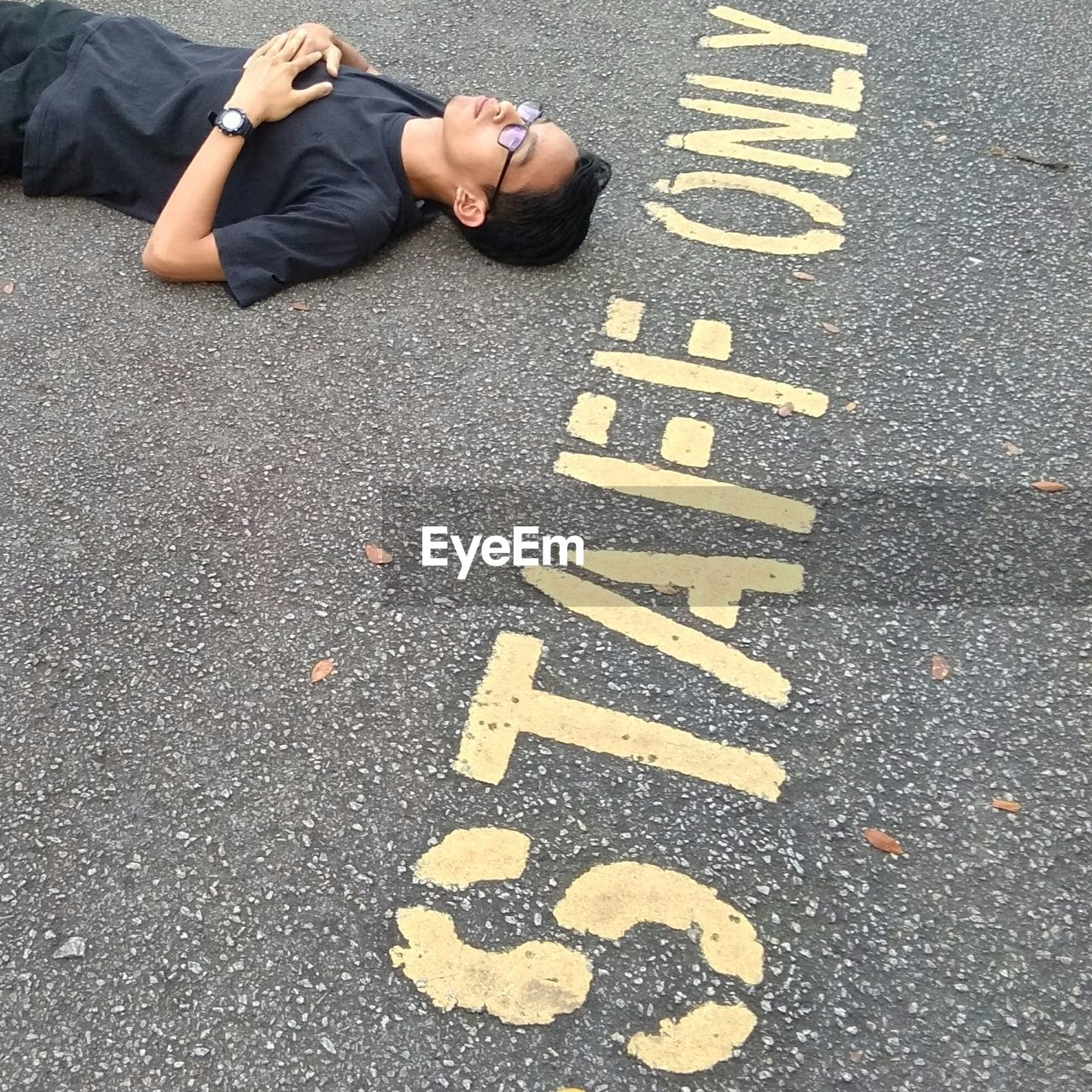 High Angle View Of Man Lying By Text On Street