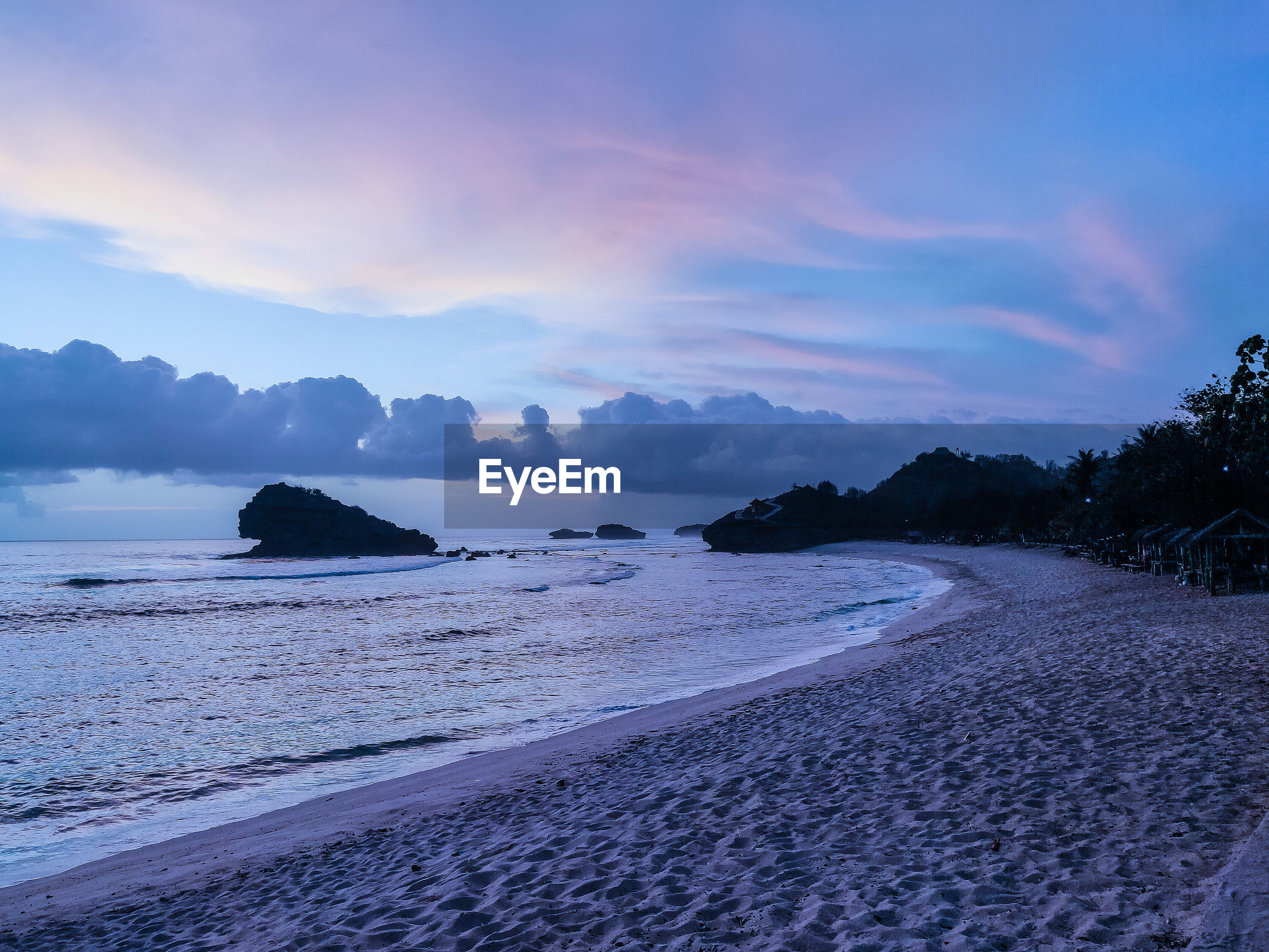 Scenic view of watukarung beach against sky at sunset