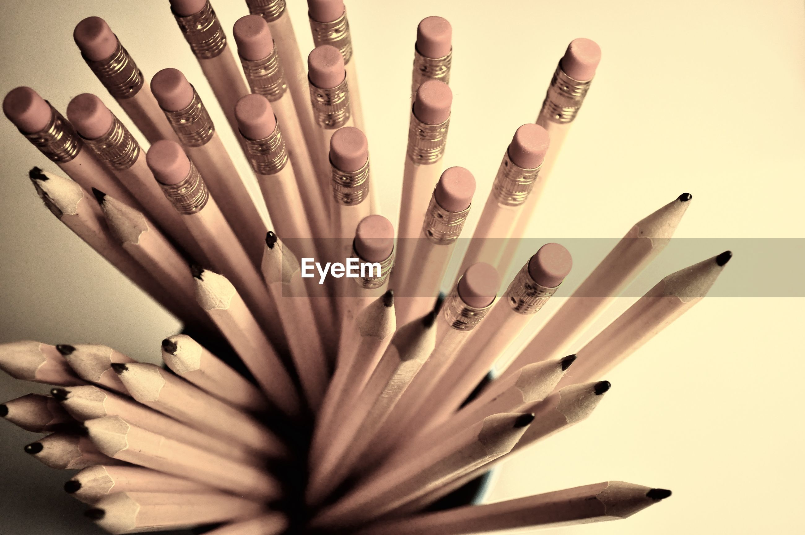 High angle view of pencils in container against beige background