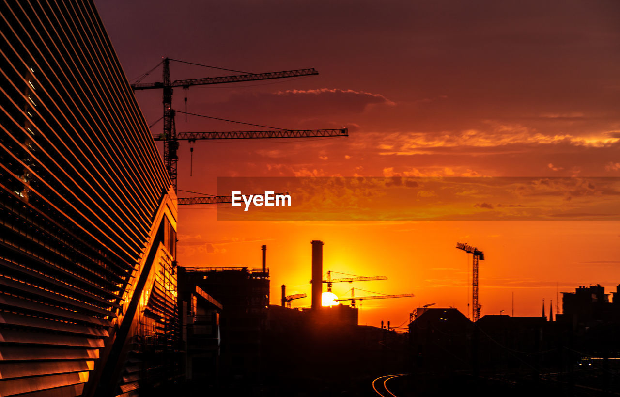 Low Angle View Of Cranes By Building At Construction Site During Sunset