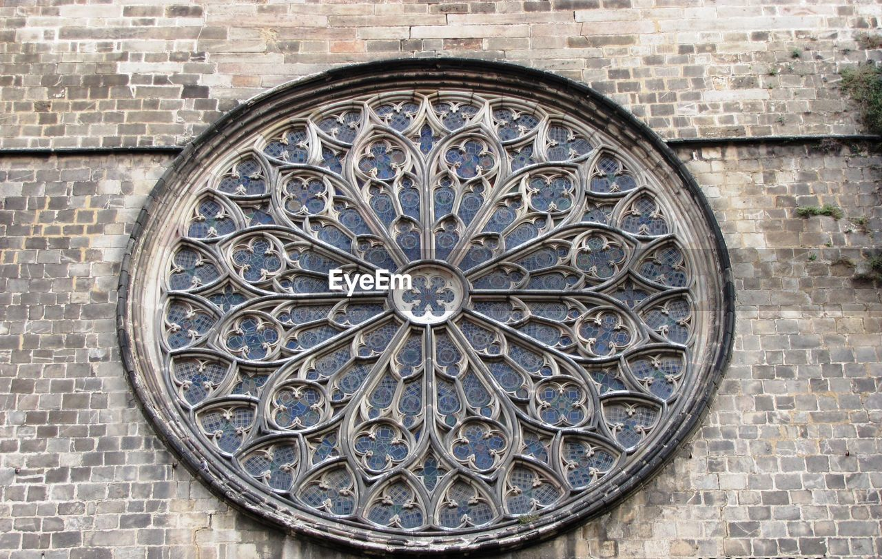 architecture, building exterior, built structure, circle, shape, geometric shape, pattern, design, wall, no people, art and craft, rose window, building, the past, history, brick wall, close-up, day, creativity, craft, outdoors, brick, ornate, stone wall, floral pattern