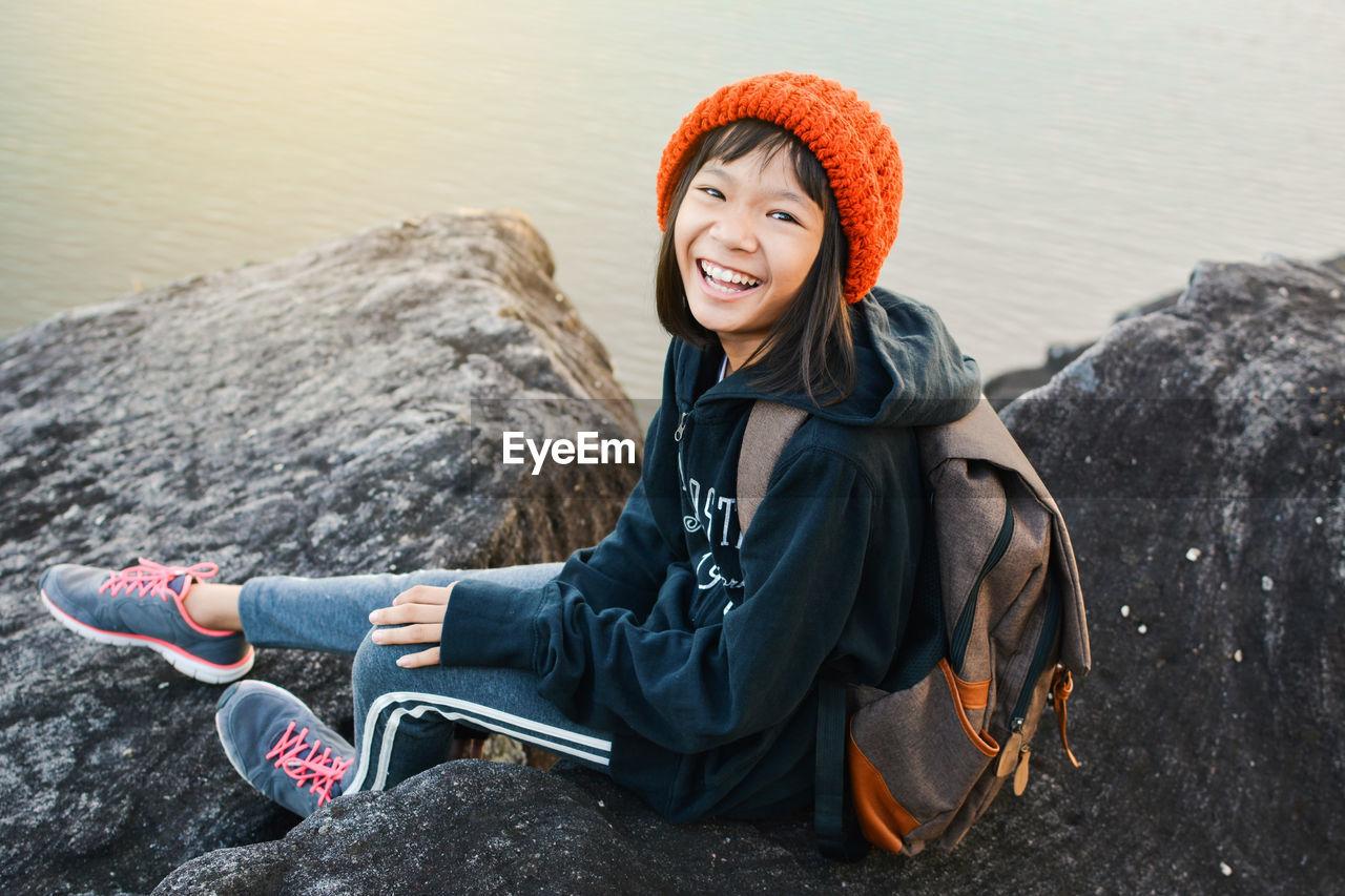 Portrait Of Girl Sitting Against Lake