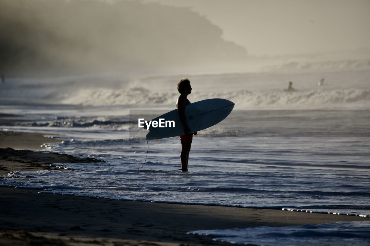 sea, water, beach, land, wave, sky, sport, surfing, real people, leisure activity, one person, motion, lifestyles, aquatic sport, surfboard, sports equipment, beauty in nature, horizon over water, skill, outdoors