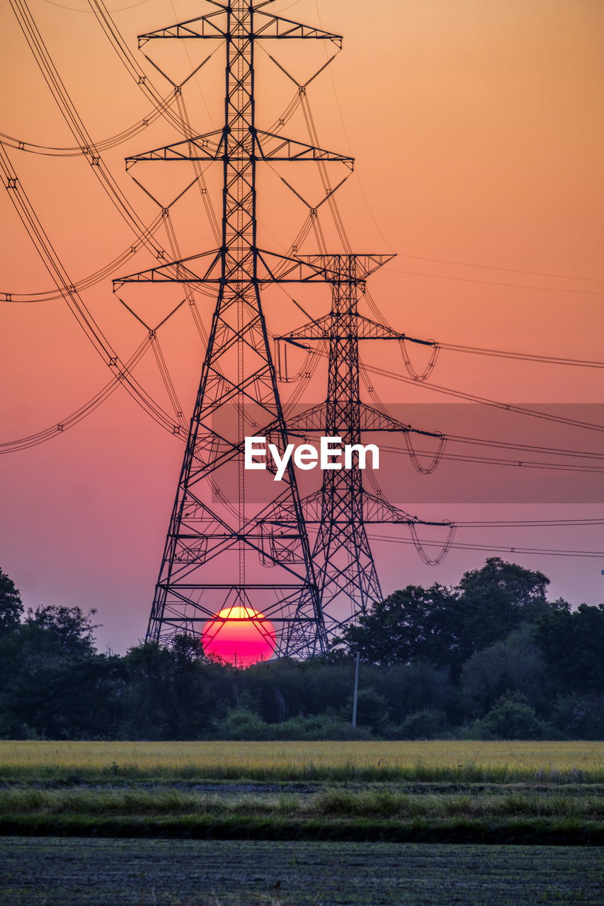 Electricity pylon substation in farmland with big red sunset for technology background