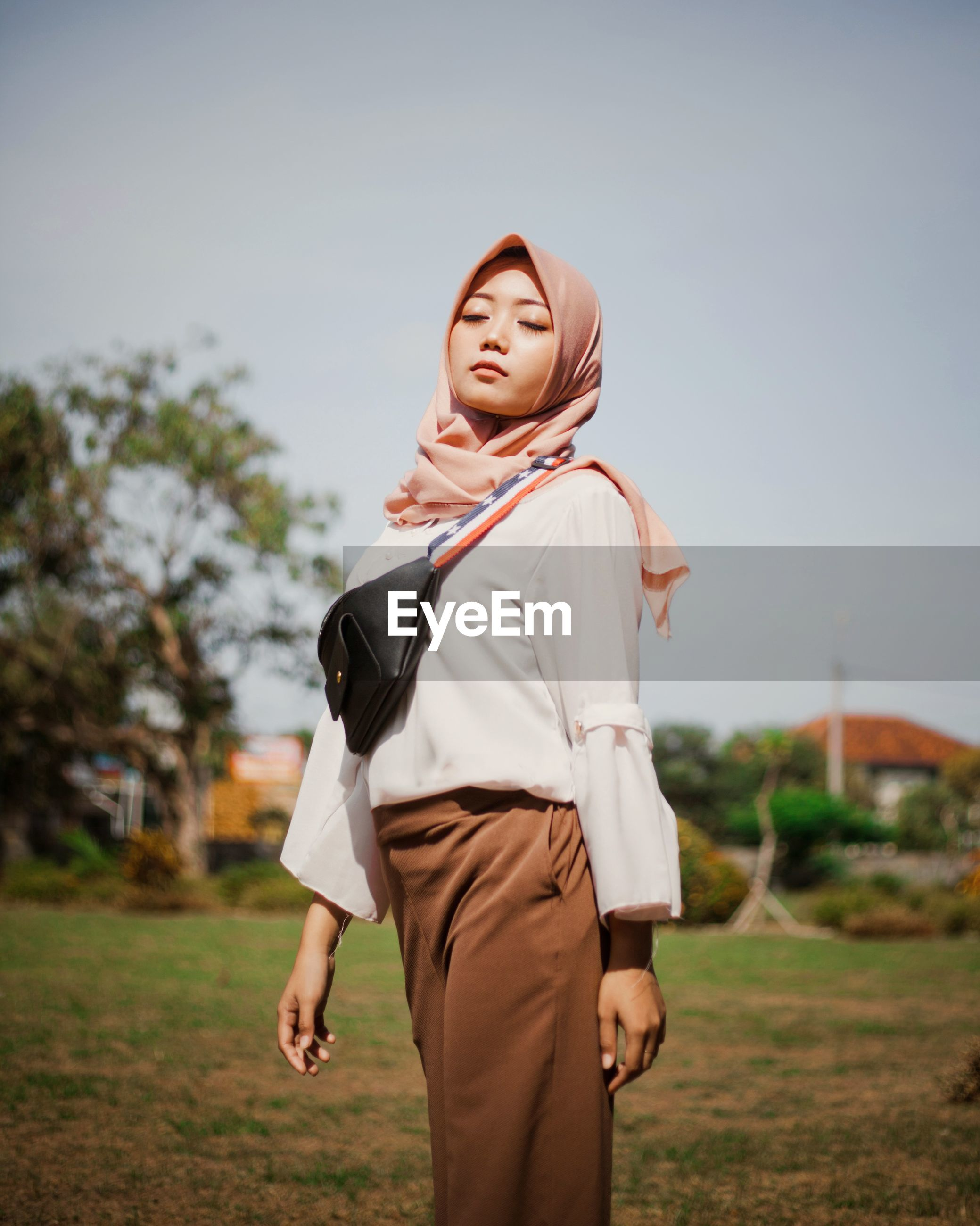 Young woman wearing hijab while standing on field against sky