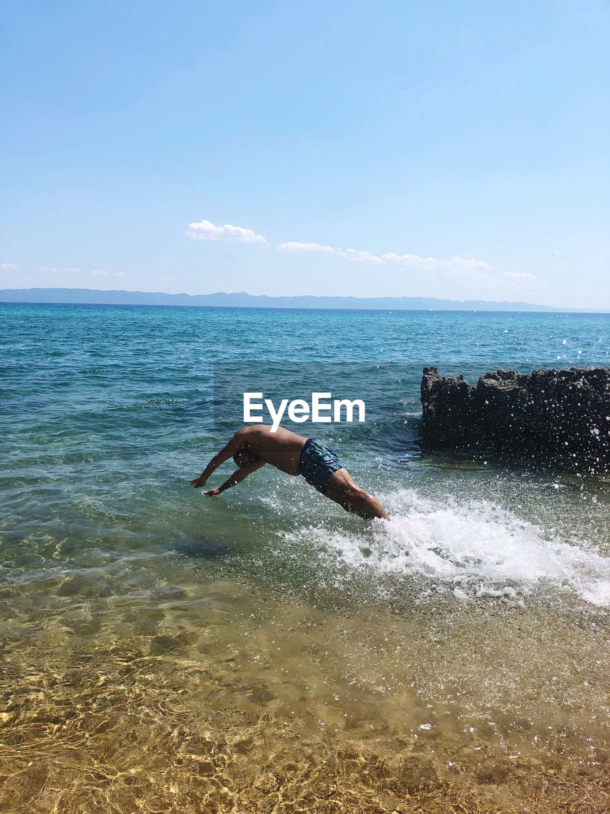 Shirtless man jumping in sea against sky during summer