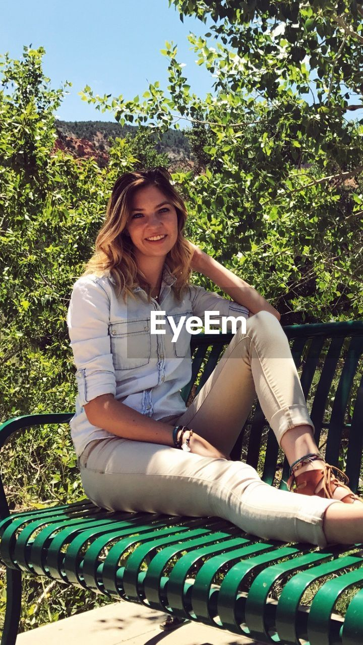 casual clothing, real people, one person, mid adult women, day, sitting, outdoors, mid adult, front view, leisure activity, smiling, looking at camera, tree, lifestyles, full length, young women, park - man made space, young adult, portrait, happiness, beautiful woman, growth, medium-length hair, nature, sky