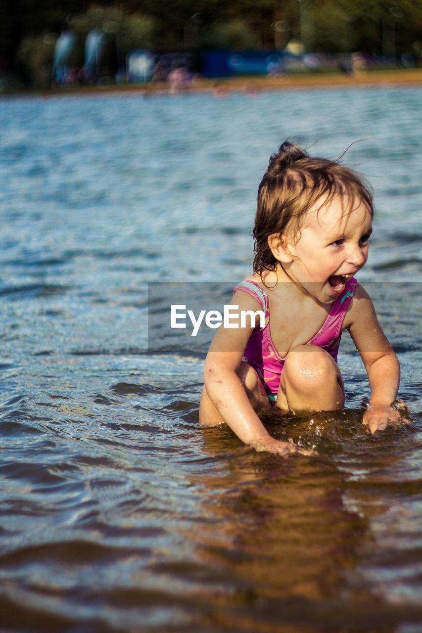 Happy Girl Crouching In Sea Shore