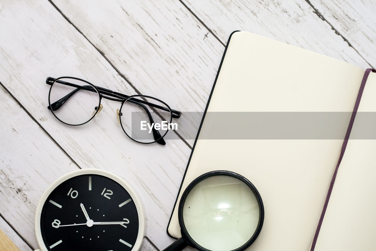 glasses, eyeglasses, table, indoors, still life, technology, no people, high angle view, number, close-up, personal accessory, communication, glass - material, instrument of measurement, accuracy, wood - material, education, white color, wireless technology, connection, eyewear