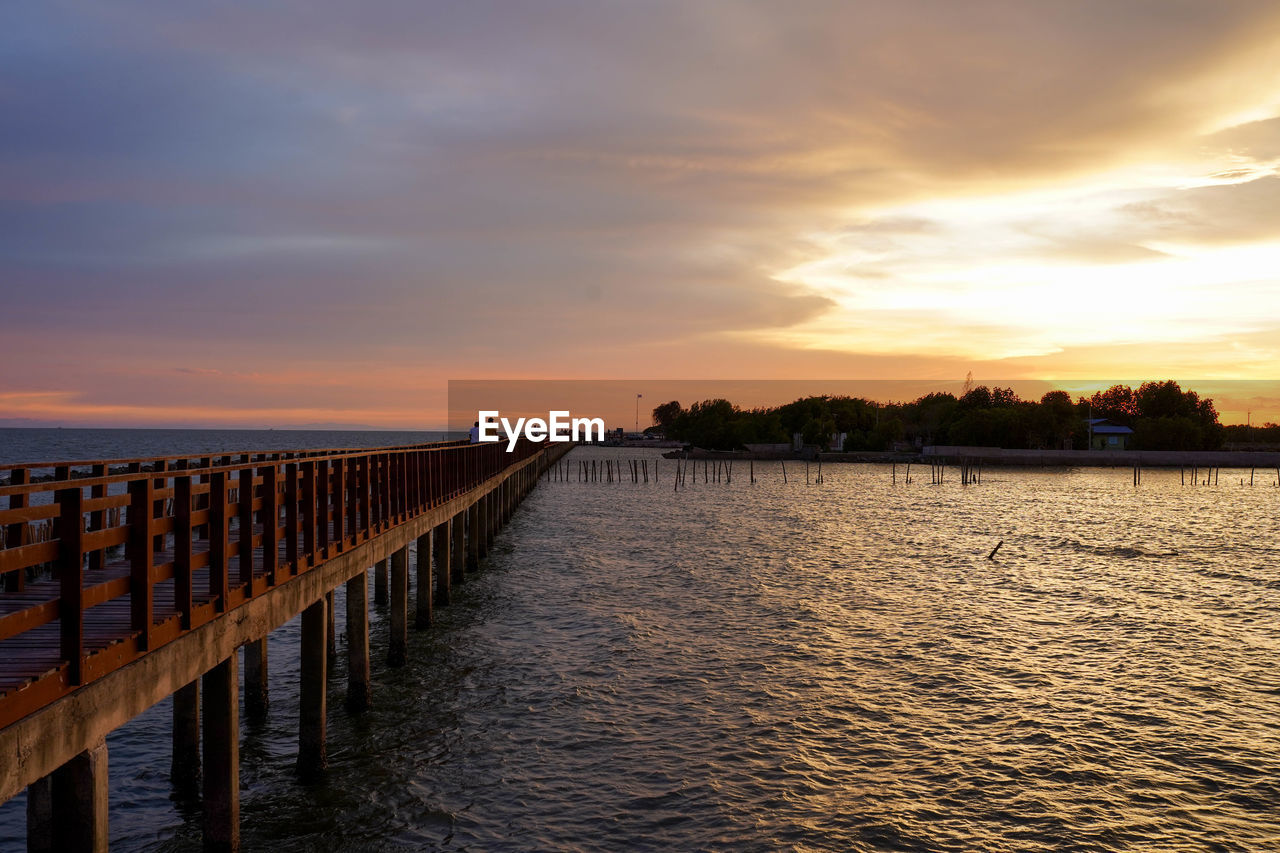 sky, water, sunset, cloud - sky, scenics - nature, beauty in nature, sea, tranquil scene, tranquility, waterfront, nature, idyllic, orange color, architecture, no people, built structure, wood - material, non-urban scene, pier, wooden post