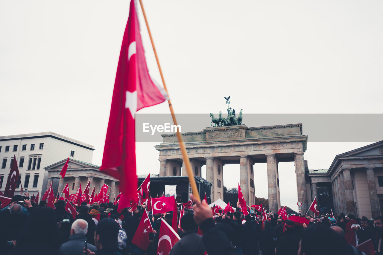 People In Front Of Flags Against Sky In City