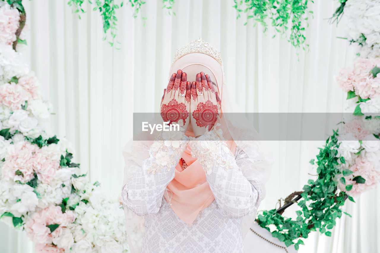 one person, real people, front view, celebration, lifestyles, portrait, event, adult, plant, waist up, leisure activity, holding, looking at camera, young adult, headshot, standing, red, flower, white color, wedding ceremony, obscured face